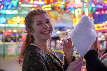 Portrait of happy redheaded teenage girl with candy floss at Oktoberfest - LBF02951