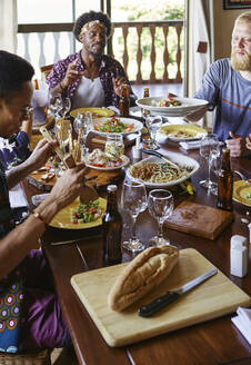 Multi-ethnic friends eating lunch while sitting at dining table in room - VEGF01739
