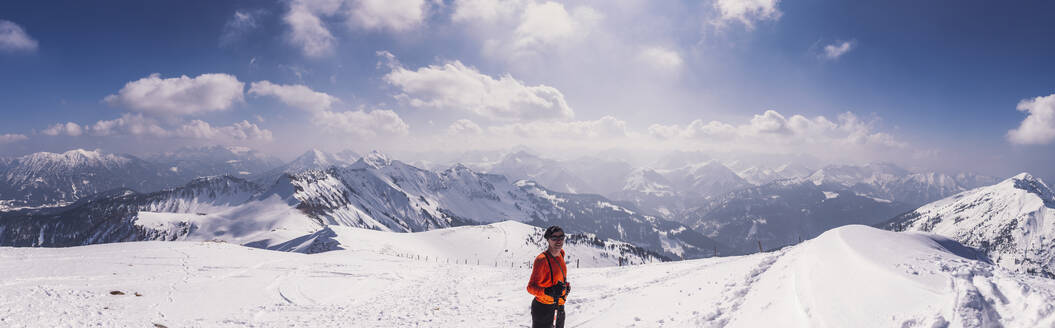 Happy male hiker standing on snow covered mountain during ski holiday at Achenkirch, Tyrol, Austria - DHEF00151