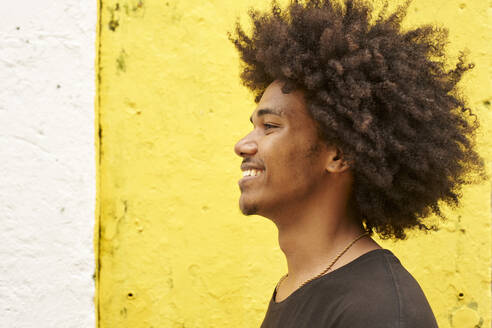 Profile of happy young man with afro against yellow wall - VEGF01751