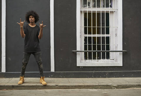 Portrait of young man with afro standing on pavement showing Rock And Roll Sign - VEGF01757