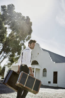 Man in old-fashioned clothes with suitcases in the countryside - RORF02024