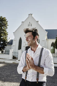 Happy man in old-fashioned clothes in the countryside praying at a church - RORF02030