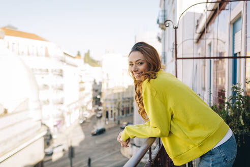 Portrait of happy young woman standing on balcony - DCRF00144