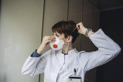 Female doctor putting on FFP3 mask - MFF05077