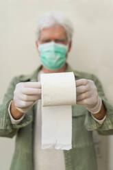 Man with face mask and protective gloves, holding roll of toilet paper - AFVF05770