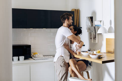 Affectionate young couple in the morning in kitchen - SODF00693