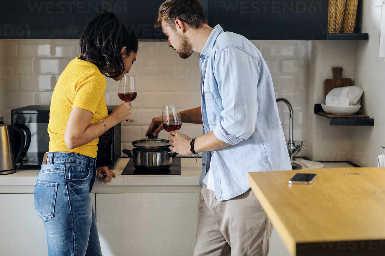 Young Couple Cooking And Drinking Wine In The Kitchen At Home Together Stockphoto