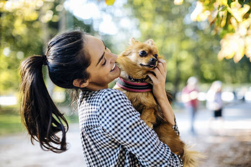 Happy young woman holding dog in a park - SODF00717
