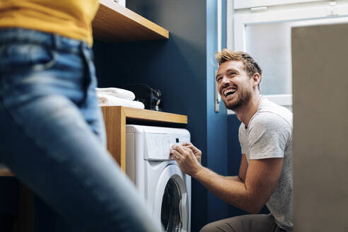 Happy young man looking at girlfriend and doing the laundry at home - SODF00726