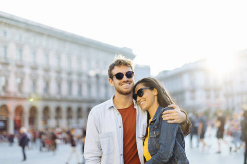 Happy young couple on a square in the city at sunset, Milan, Italy - SODF00735