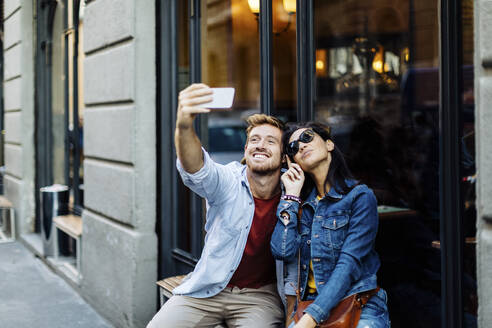 Happy young couple taking a selfie in the city, Milan, Italy - SODF00738