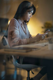 Young woman sitting at desk in office looking at smartphone - JSRF00914