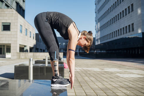Sporty young woman with leg prosthesis practising in the city - MEUF00133