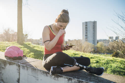 Sporty young woman with leg prosthesis sitting on a wall using cell phone - MEUF00154