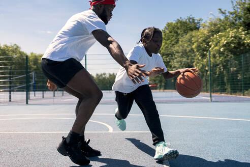 Father and son playing basketball on basketball court - JPIF00508