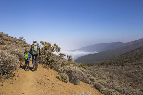 Rear view of a father with his son trekking in the Arenas Negras area, Teide National Park, Tenerife - IHF00289