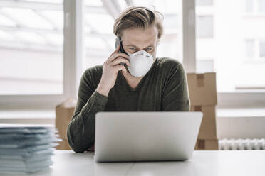Businessman wearing protective mask and using laptop and cell phone - JOSEF00114
