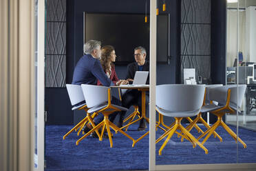 Two businessmen and businesswoman working together on a project in office - RBF07138