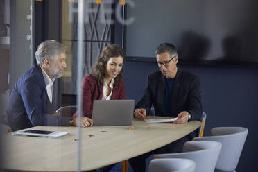 Two businessmen and businesswoman working together on a project in office - RBF07141