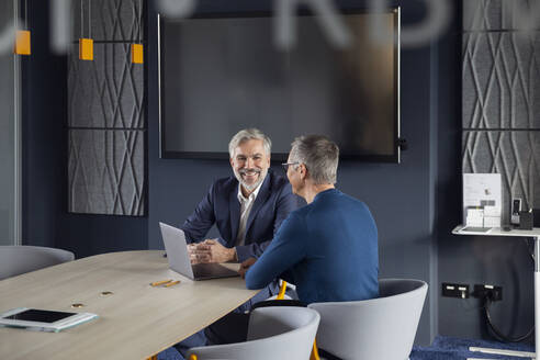 Two smiling businessmen working together on a project in office - RBF07144