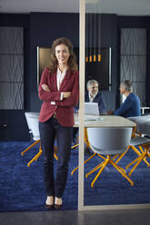 Portrait of confident businesswoman in office with colleagues in background - RBF07153