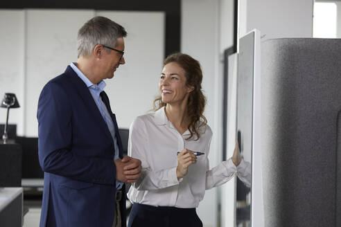 Smiling businesswoman and businessman working together at a board in office - RBF07168