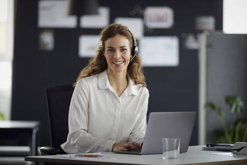 Portrait of smiling businesswoman with headset and laptop at desk in office - RBF07177