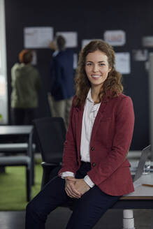 Portrait of smiling businesswoman sitting on desk in office with colleagues in background - RBF07186