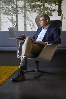 Businessman sitting in armchair in office using laptop - RBF07204