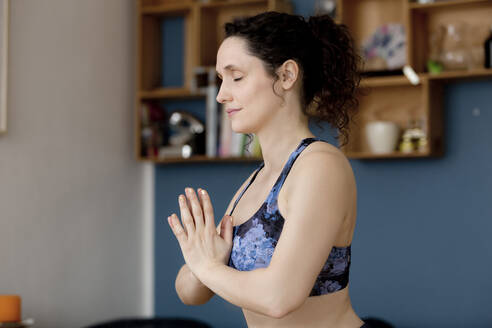 Young woman with closed eyes and anjali mudra in yoga pose at home - FLLF00423