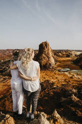 Rear view of female friends looking at volcanic landscape in Dallol Geothermal Area, Danakil Depression, Ethiopia, Afar - LHPF01163