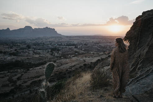 Full length of woman standing at Gheralta Mountains during sunset, Ethiopia, Central Tigray, Hawzen - LHPF01169