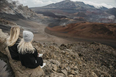Rear view of female friends sitting at Haleakala Crater, Maui, Hawaii, USA - LHPF01193
