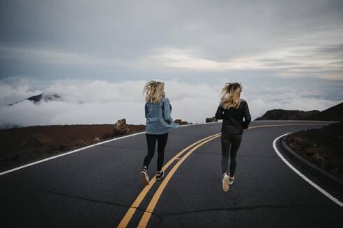 Rear view of friends running together on street at Haleakala Volcano, Hawaii, Maui, USA - LHPF01196