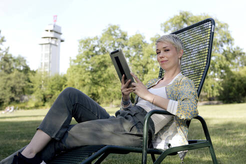 Portrait of smiling woman with digital tablet sitting on deck chair in a park - FLLF00432