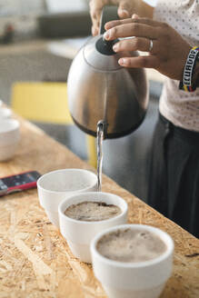 Close-up of woman working in a coffee roastery pouring hot water into coffee cups - JPIF00527