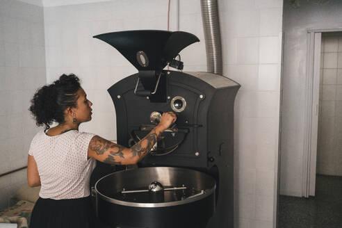 Woman working in a coffee roastery operating machine - JPIF00551