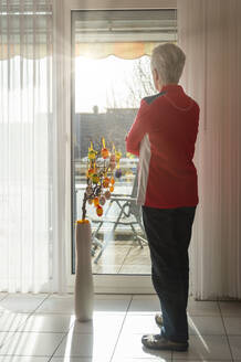 Senior woman standing at closed balcony and looking out of the window - FRF00907