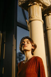 Portrait of young woman with closed eyes leaning on a column - TCEF00261