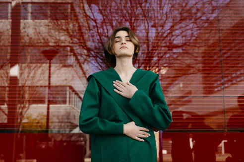 Young woman with closed eyes wearing green coat in front of a glass pane - TCEF00300