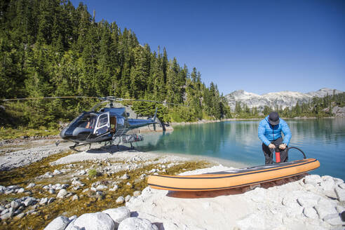 Adventurous man pumps up inflatable SUP next to a remote lake. - CAVF77436