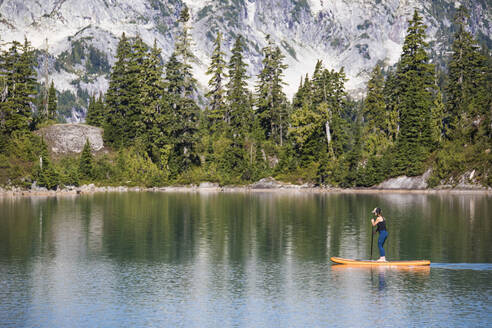 Side view of active woman paddle boarding on mountain lake. - CAVF77439