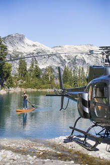 Active woman paddle boards on remote lake accessed by helicopter. - CAVF77442