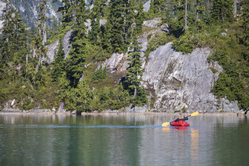 Rear view of retired woman paddling a packraft on remote lake. - CAVF77445