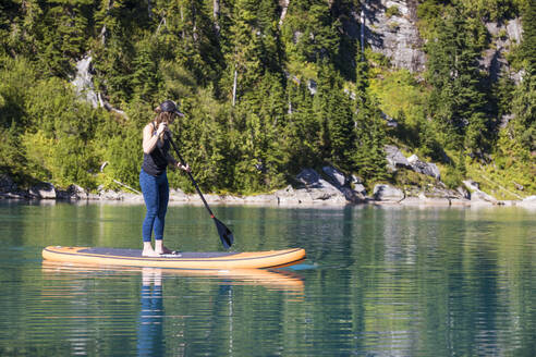 Young woman paddle boarding on remote lake. - CAVF77448