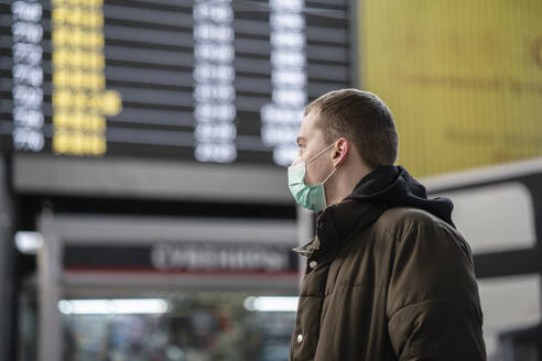 Young man with face mask at train station in the city - VPIF02125