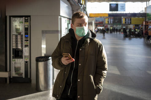 Young man with face mask at train station in the city, holding smartphone - VPIF02128