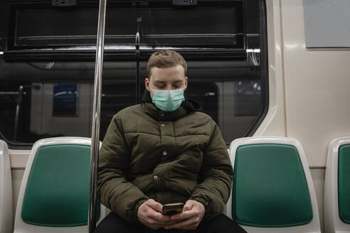 Young man in commuter train, wearing face mask, using smartphone - VPIF02134