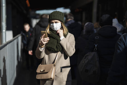 Woman with face mask standing at bus stop, using smartphone - VPIF02137